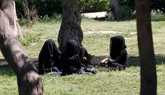 Veiled women sit as they chat in a garden in the northern province of Raqqa